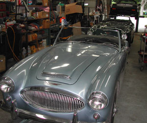 60 Austin Healey leading a row of cars in the bay waiting for work